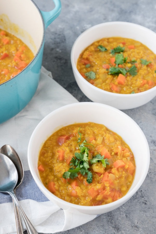two bowl of red lentil dal next to dutch oven