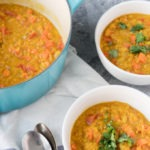 red lentil dal in two bowls next to blue dutch oven full of dal
