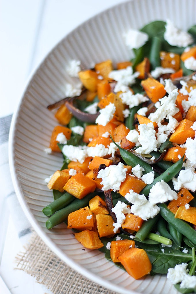 close up of pumpkin feta and spinach salad ingredients in a bowl - feta cheese, green beans, pumpkin and red onion