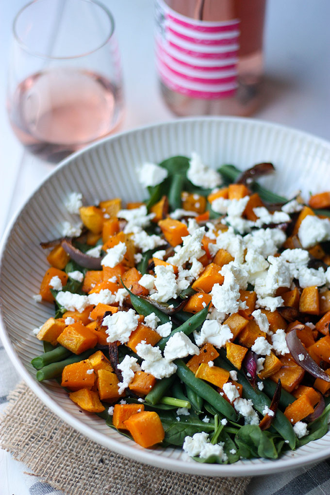 pumpkin feta and spinach salad pictured in white bowl in front of wine bottle and glass