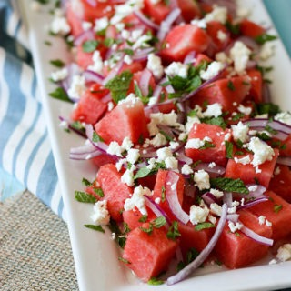 watermelon mint feta salad on white rectanuglar plate on bright blue background