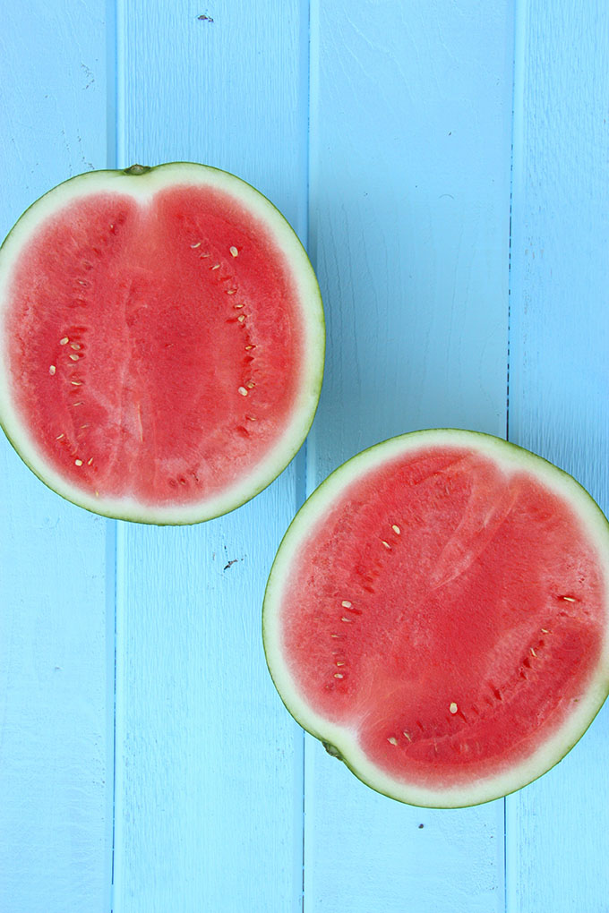 two watermelon halves on a bright blue wooden board