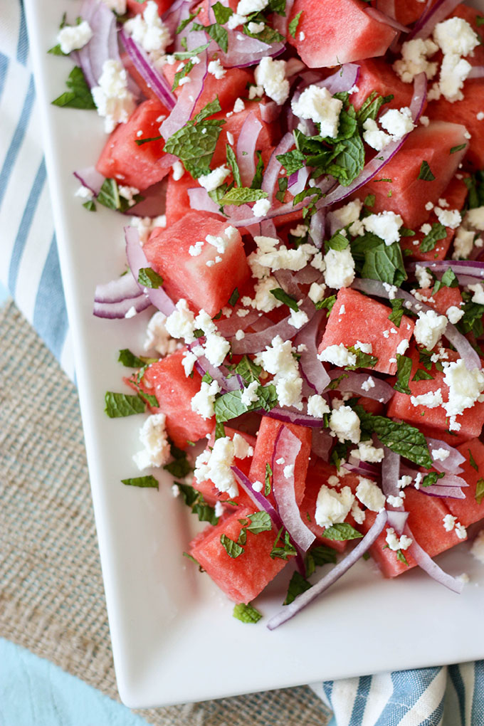 watermelon mint feta salad on a white plate; white plate is set on a blue and white napkin