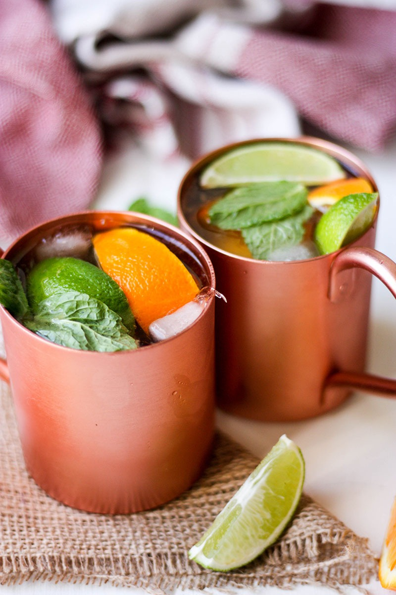 citrus ginger dark and stormy cocktails in copper mugs on hessian square
