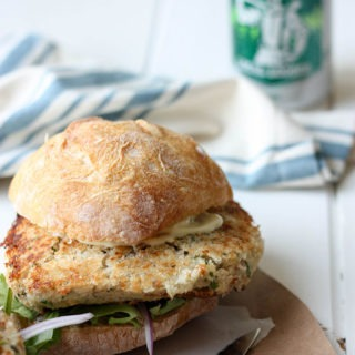 salmon burger topped with a ciabatta roll on a brown piece of paper