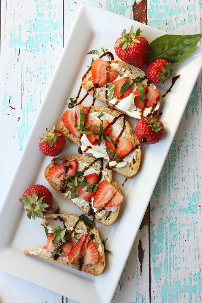 long white rectangular plate of strawberry bruschetta on a turquoise board