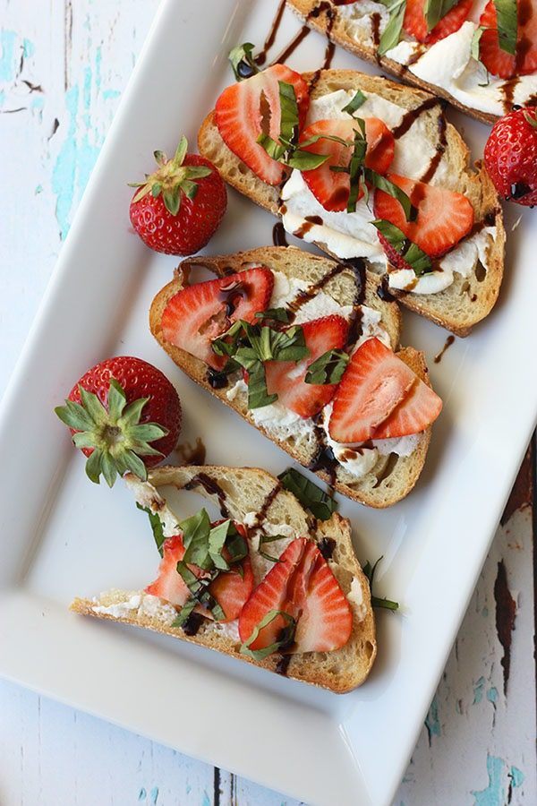 white plate lined with pieces of strawberry bruschetta