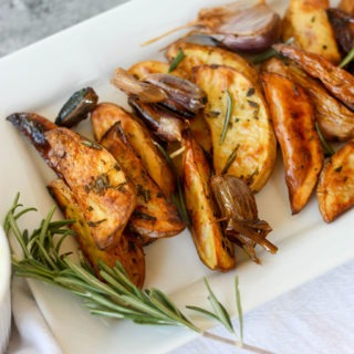 oven baked fries on white plate with rosemary sprig