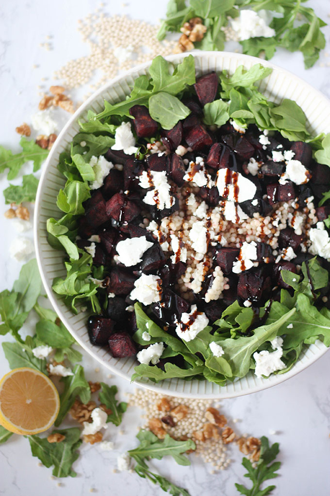 beetroot goat cheese salad in white bowl surrounded by ingredients