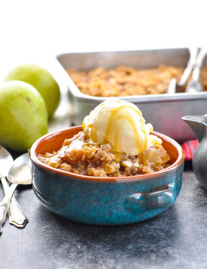 pear crisp in blue bowl with pears in background