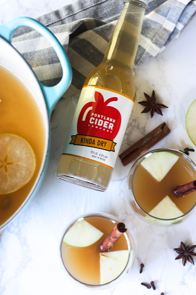 hot spiced apple cider in glasses on marble board, cider bottle and dutch oven in image