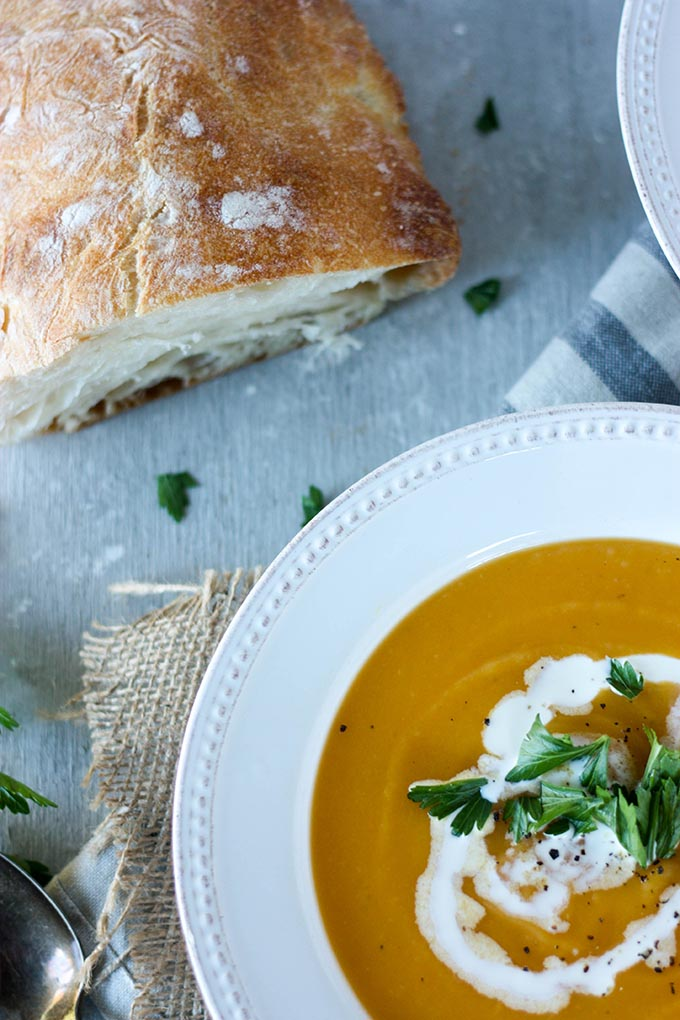 bowl of pumpkin sweet potato soup next to crusty loaf of bread