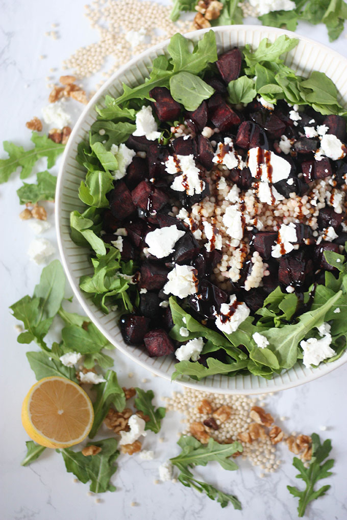 beetroot goat cheese salad in salad bowl or marble board. bowl surrounded by couscous, walnuts and arugula