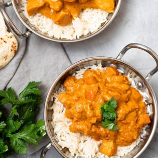 two dishes of chicken massaman curry on grey board