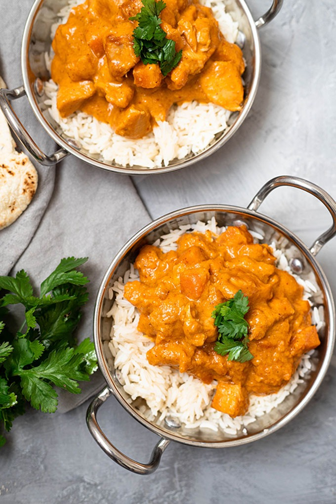 two dishes of chicken massaman curry in copper dishes
