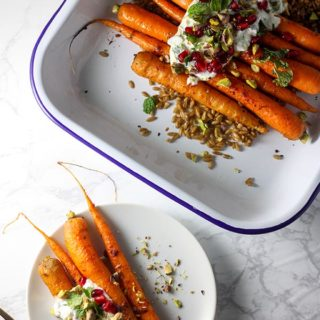 harissa roasted carrots on a white plate next to carrots in a blue and white enamel baking tray
