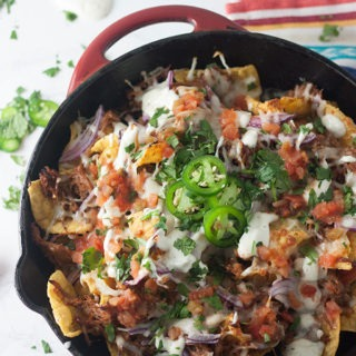 Red skillet full of pulled pork nachos on a brigh coloured towel