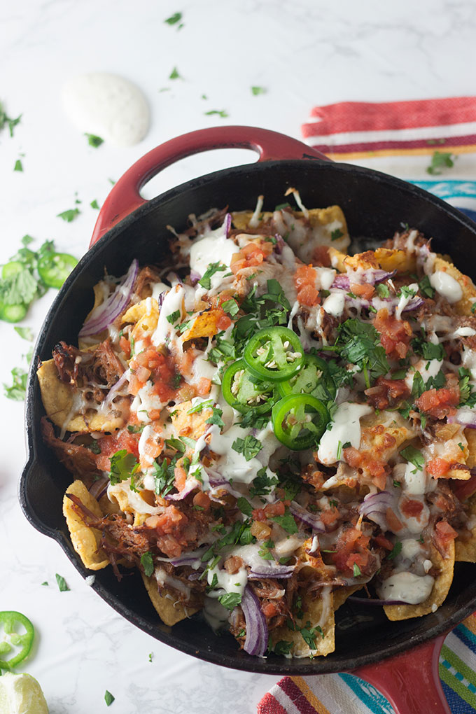 close up of pulled pork nachos in red skillet on colourful napkin