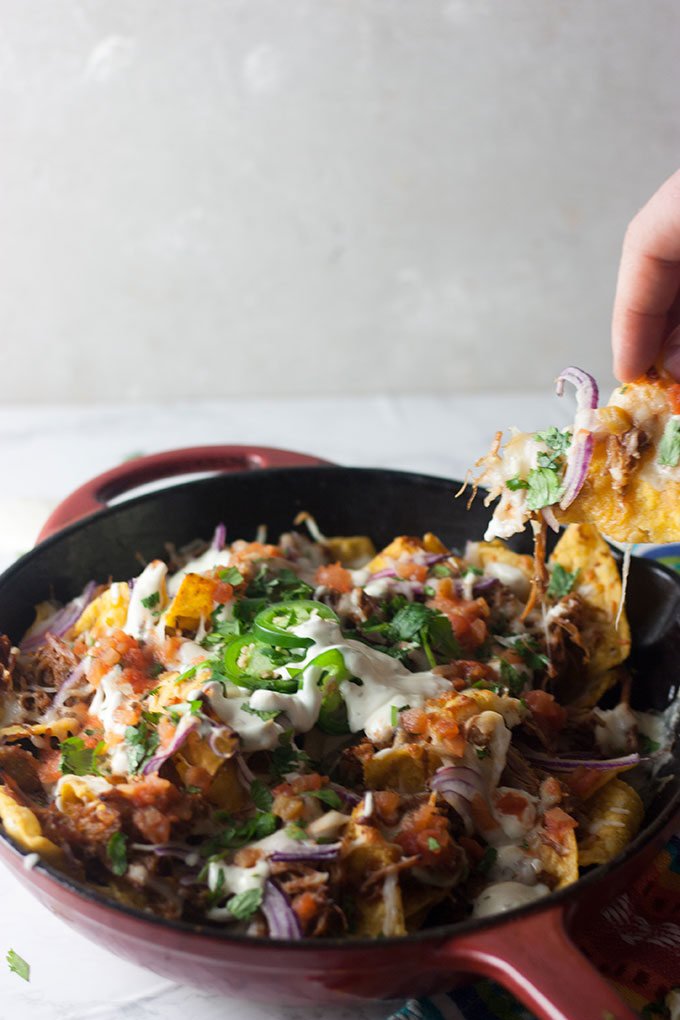 hand reaching out to take a nacho chip from red skillet