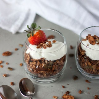 one glass pot of chocolate granola topped with yogurt and strawberries