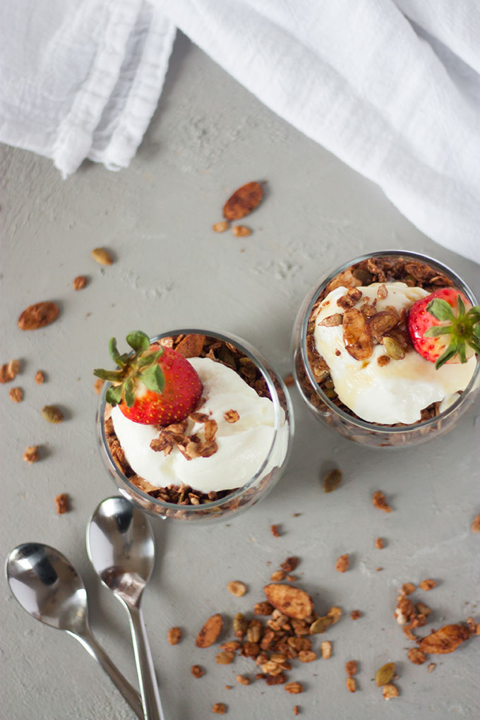 overhead of two chocolate granola pots with yogurt and berries