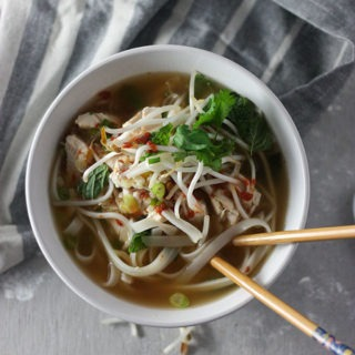 bowl of chicken pho on grey napkin with chopsticks in bowl