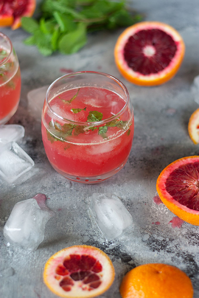 single tumbler, surrounded by blood oranges and ice cubes