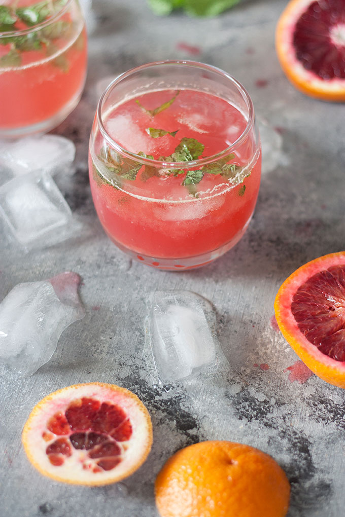 one single blood orange cocktail in small tumbler, blood orange segments on right