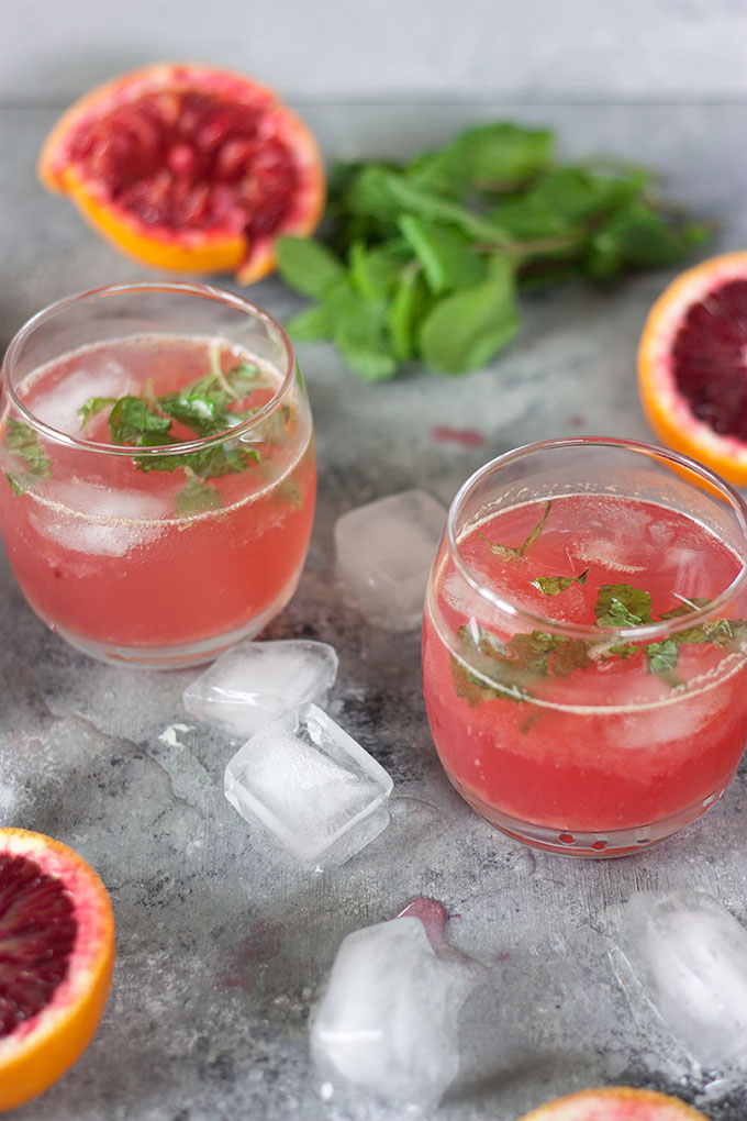 two blood orange cocktails on a grey board with cut winter citrus