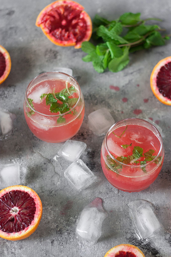 two blood orange cocktails on dark grey board, surrounded by blood orange segments, mint and ice cubes