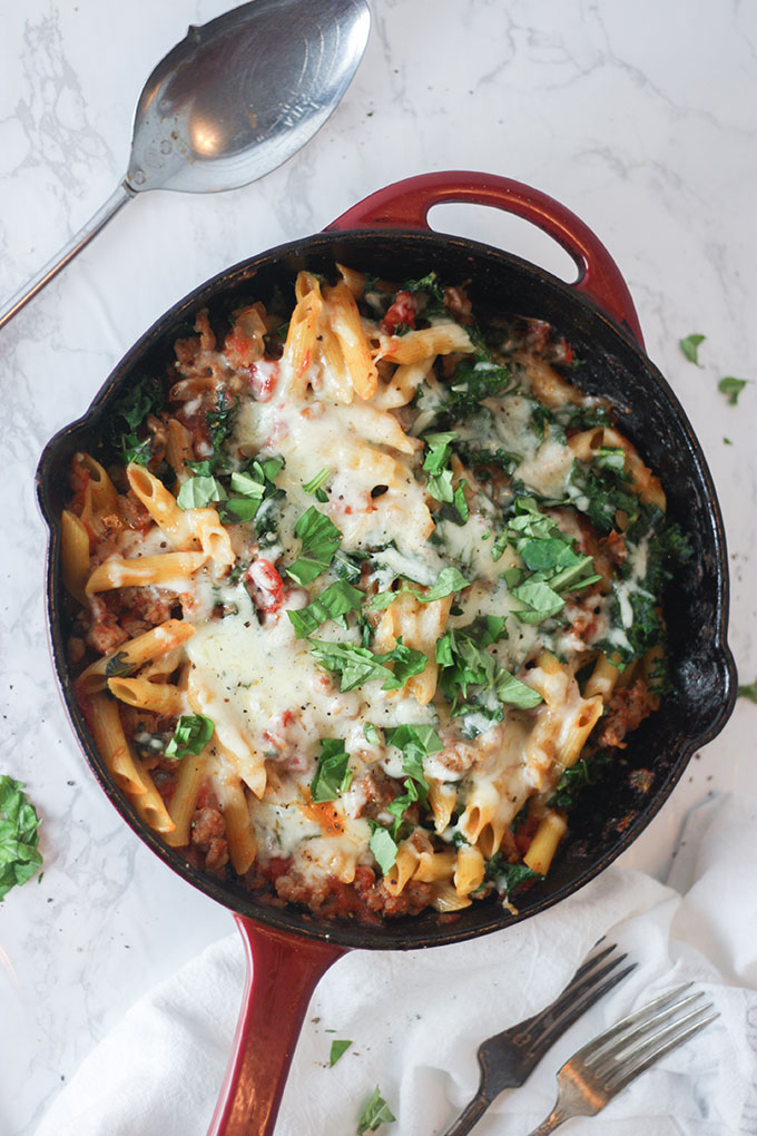 a red skillet with baked pasta, italian sausage and melted cheese