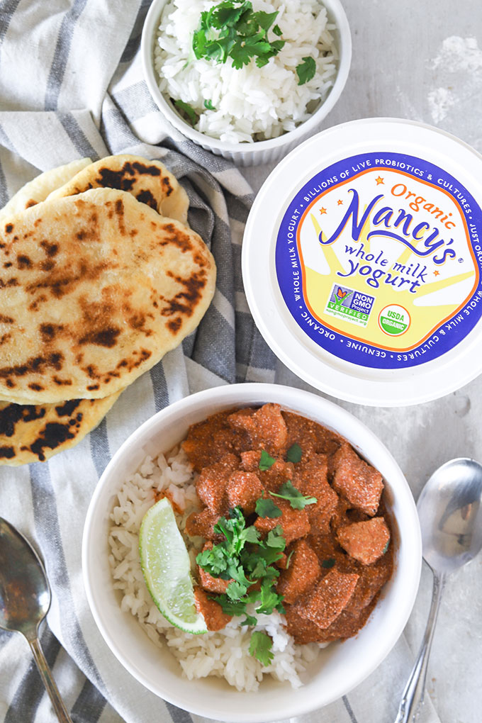 one bowl of chicken yogurt curry with naan on the left and a yogurt container