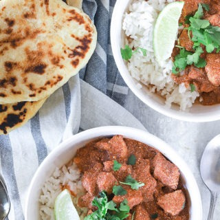 two bowls of chicken yogurt curry with naan bread on a napkin
