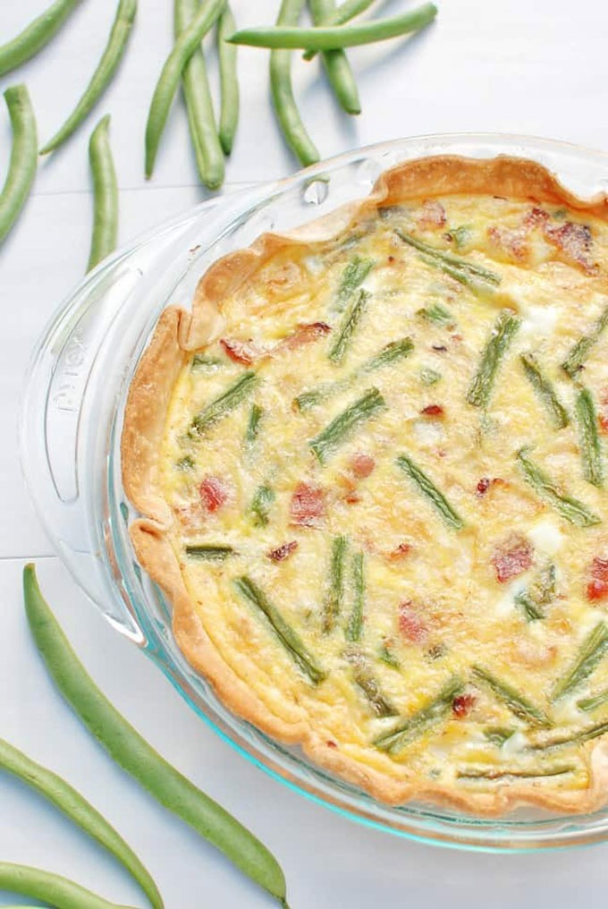 green bean quiche in glass dish, single green beans on board