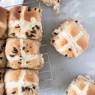 two single hot cross buns next to wire rack with 3 hot cross buns on it