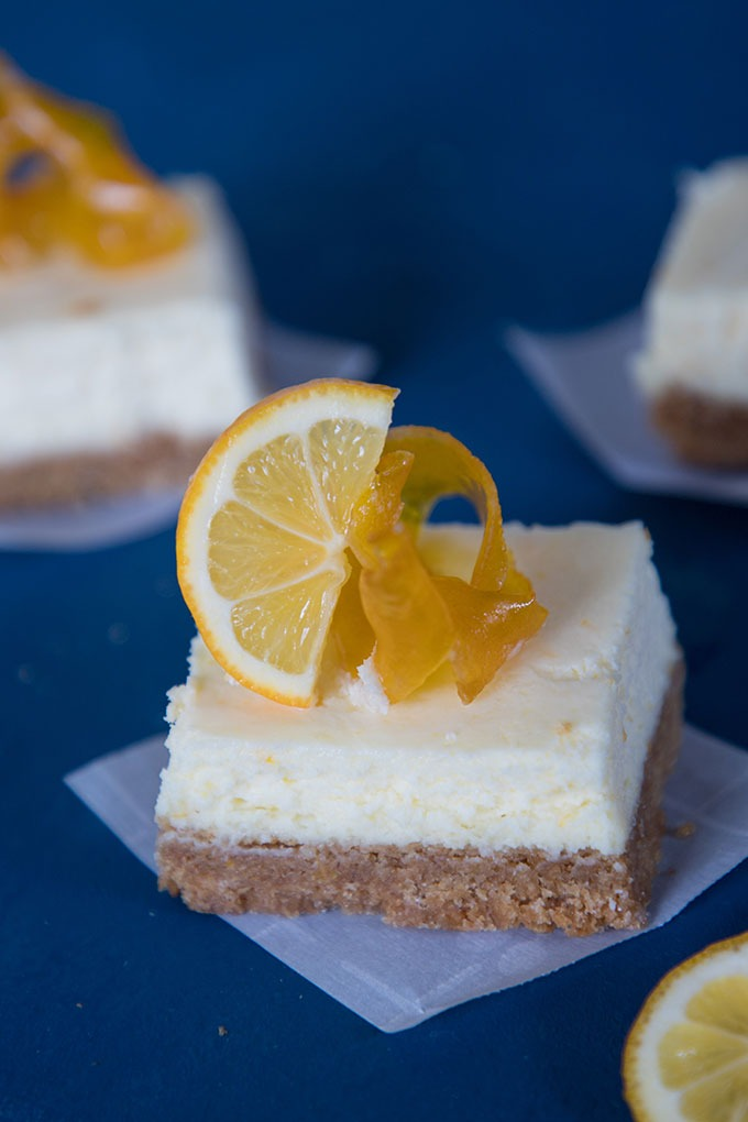 One slice of the lemon cheesecake bars on parhment paper