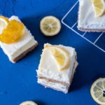 three pieces of lemon cheesecake bars on a board, three pieces of lemon slices and wire rack