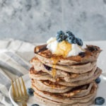 stack of kefir pancakes with maple syrup being poured over from top