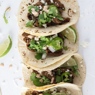 four steak tacos lined up topped with jalapeno, cilantro, onion and cojito