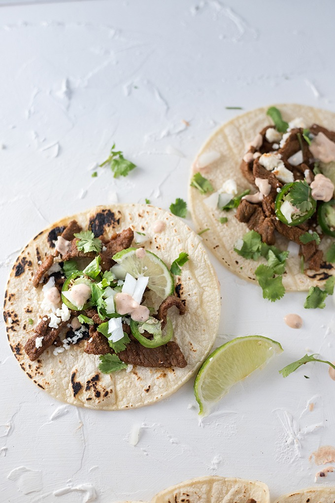 two steak tacos on a white board, topped with queso, cilantro, lime wedges and white onion