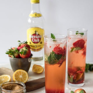 two tall glasses of strawberry mojitos, havana club bottle in background, lemonand strawberries on marble board
