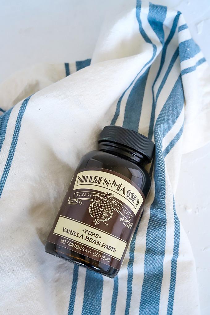 bottle of nielsen-massey vanilla bean paste on blue and white napkin
