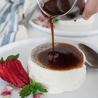 espresso syrup being poured over a vanilla bean panna cotta on white plate