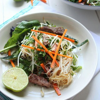 one bowl of vietnamese beef salad on a cream plate, garnished with lime wedge