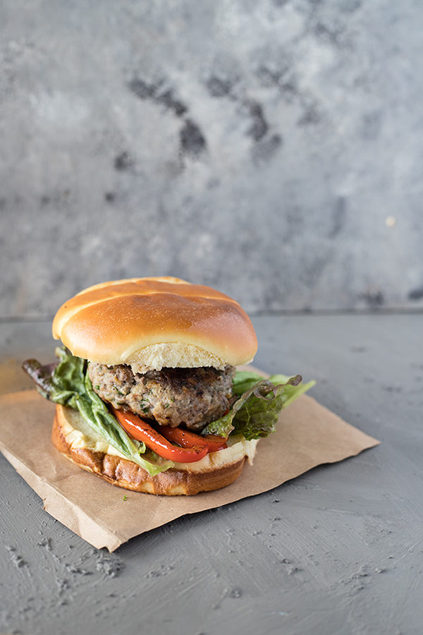 single lamb burger with feta on brown parchment paper