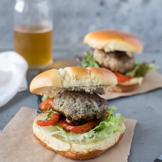 two lamb burgers with feta on brown parchment paper, in front of glass of beer