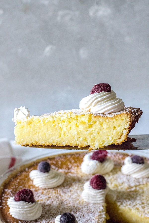 slice of lemon coconut tart being held up in front of rest of pie