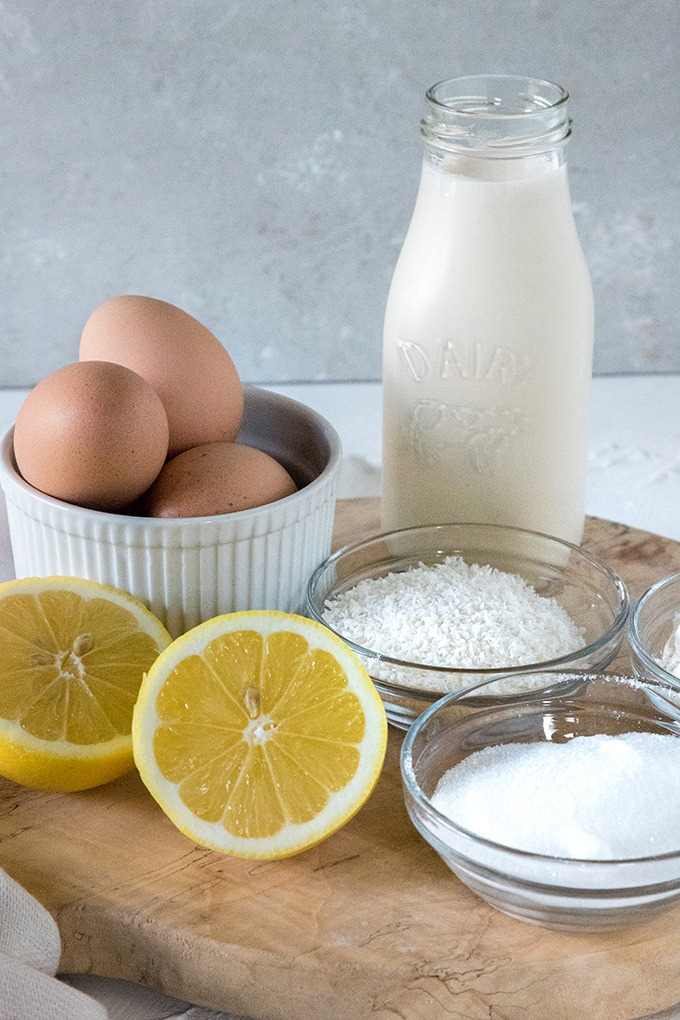 lemon coconut tart ingredients on wood board - eggs, lemons, flour, cream, sugar and coconut