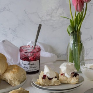 plate of lemonade scones with jam and cream in front of vase of tulips and jam jar