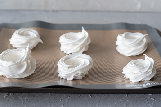 6 vanilla meringues on a non stick silicone baking mat ready for baking